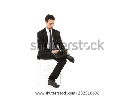 Good looking smart business man in a black and white suit and tie  posing with his legs crossedlooking down at a  small computer - stock photo