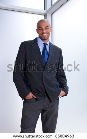 Good-looking smiling businessman standing near office window.