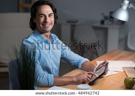 Good looking smiling young man using tablet.
