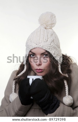 good looking woman in a winter clothes and a hot drink in her hands to keep warm