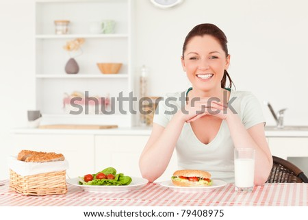 Good looking woman ready to eat a sandwich for lunch in her kitchen - stock photo
