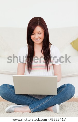 Good looking woman relaxing with her laptop while siting on a carpet in the living room - stock photo