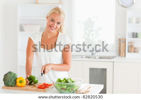 Good looking woman slicing pepper in her kitchen - stock photo
