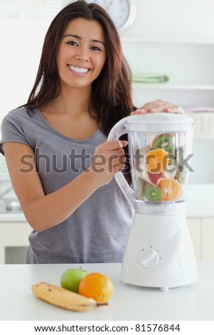Good looking woman using a blender while standing in the kitchen - stock photo