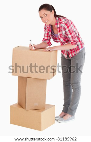 Good looking woman writing on cardboard boxes with a marker while standing against a white background