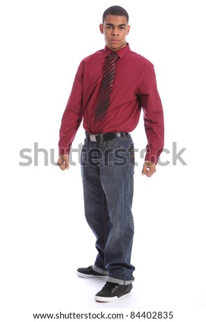 Good looking young African American man standing with serious expression on his handsome face wearing jeans, long sleeved shirt and necktie. - stock photo