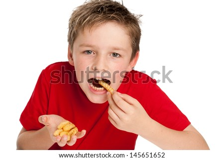 Good looking young boy eating french fries chips. Isolated on white background. - stock photo