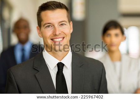 good looking young business man with colleagues on background - stock photo