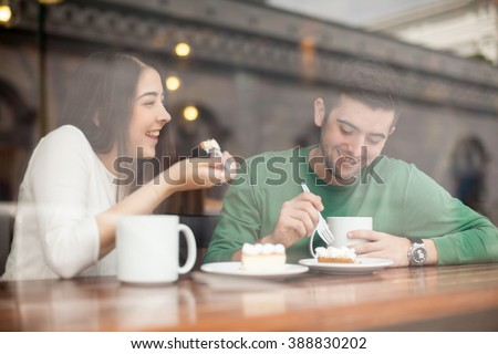Good looking young couple laughing and having a good time on a date in a coffee shop - stock photo