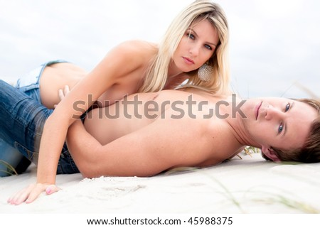 Good looking young couple lying down topless on the beach. - stock photo