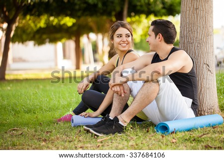 Good looking young couple with exercise mats sitting next to a tree and flirting while taking a break from working out - stock photo