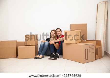Good looking young Hispanic couple moving into their new home. Lots of copy space - stock photo