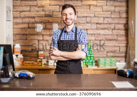 Good looking young male cashier standing at the checkout counter and greeting customers with a smile - stock photo