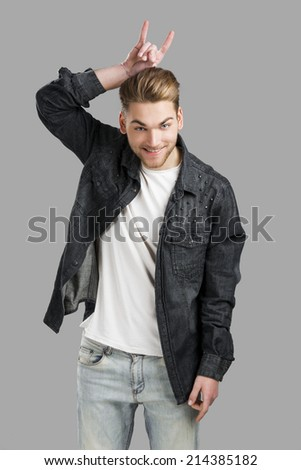 Good looking young man smiling and making a funny face, isolated over a gray background - stock photo