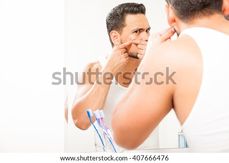 Good looking young man standing close to a mirror in the bathroom and squeezing a pimple on his face - stock photo