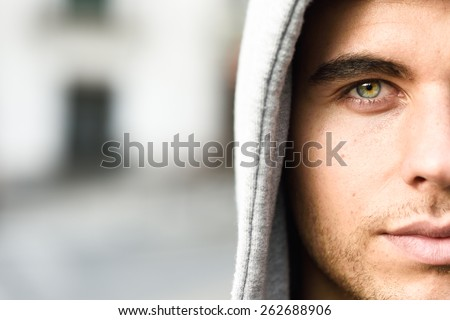 Good looking young man with blue eyes in the street wearing hooded jacket - stock photo