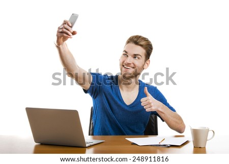Good looking young man working in the office and taking a selfie  - stock photo