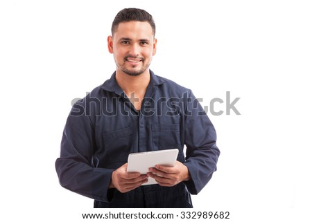 Good looking young mechanic in overalls using a tablet computer for work and smiling - stock photo