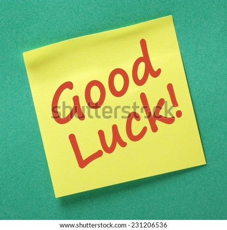 Good Luck message written on a yellow sticky note attached to a green paper background - stock photo