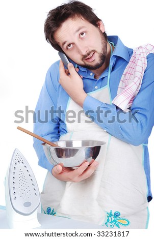 Good man is ironing, cooking and speaking on phone