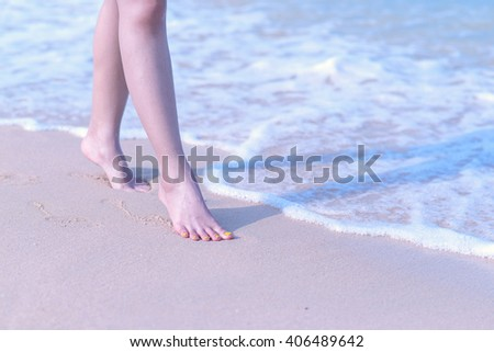 Good morning Beach travel - woman walking on sand beach leaving footprints in the sand. Closeup detail of female feet and golden sand on beach