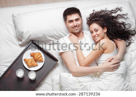 Good morning! Love and comfort. Breakfast in bed. Overhead of happy beautiful young couple lying on the bed. Top view. - stock photo