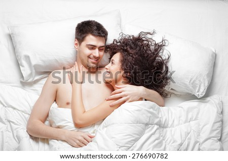 Good morning! Love and comfort. Overhead of happy beautiful young couple lying on the bed laughing and hugging. Top view. - stock photo