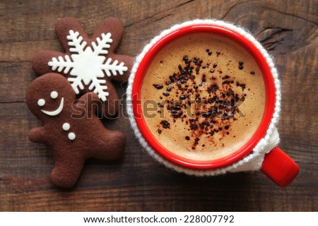Good morning or Have a nice day Merry Christmas message concept - red cup of frothy coffee in knitted cup holder and traditional decorated festive snowflake and gingerbread man chocolate cookies  - stock photo