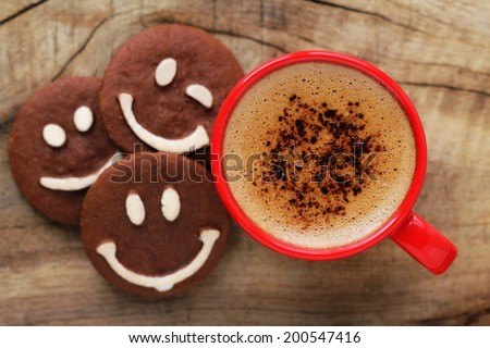 Good morning or Have a nice day message concept - bright red cup of frothy coffee with smiling chocolate cookies - stock photo