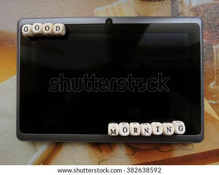 Good morning! - Small wooden cubes and a tablet on a light background
