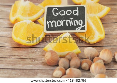 Good morning. Tasty morning. Orange morning. Orange pieces with nuts  on wooden background.  - stock photo