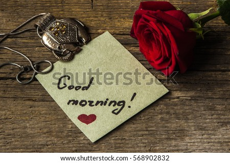 Good morning text on a paper, red rose flower and decoration elephant.