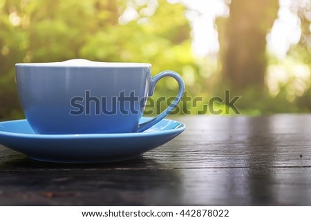 Good Morning with Coffee in blue cup on wooden table and sunlight in garden.