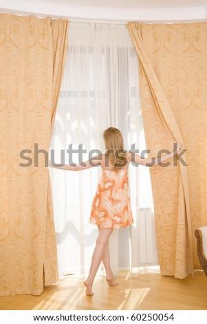 Good Morning ! - woman in bedroom beside window - stock photo