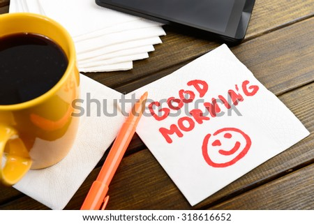 Good morning writing on white napkin around coffee pen and phone on wooden table - stock photo