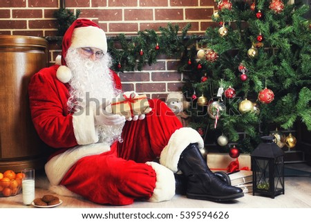 good-natured Santa Claus in a red suit and white beard at the Christmas tree