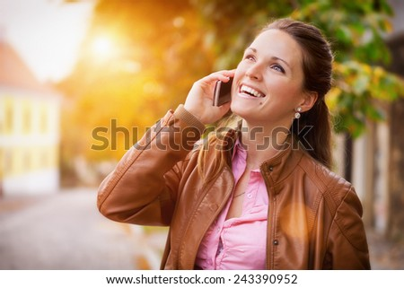 Good news / business women use a cell phone in the city - stock photo