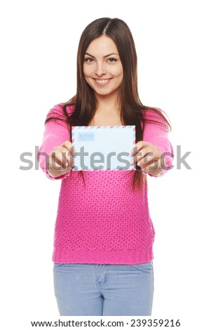 Good news concept. Happy woman in pink sweater giving you blank air mail envelope, over white background. Focus at girl.