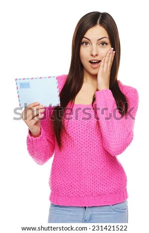 Good news concept. Surprised happy woman in pink sweater showing blank air mail envelope, over white background - stock photo