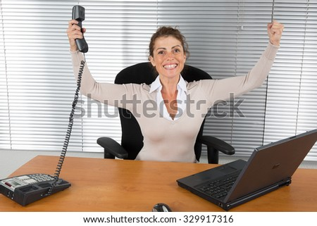 Good news -Successful business woman with arms up - stock photo