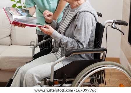 Good nurse viewing a photo album with her disabled ward