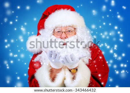 Good old Santa Claus blowing a snow over blue background. Snowfall, snowflakes. The magic of Christmas. - stock photo