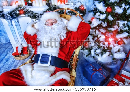 Good old Santa Claus sitting in a rocking chair in the room by the fireplace and Christmas tree, beautifully decorated for Christmas.