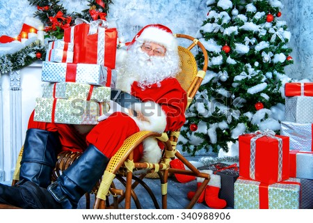Good old Santa Claus sitting in a rocking chair with a lot of gift boxes. He is in a beautiful room with Christmas tree. - stock photo