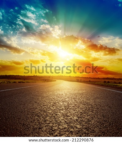 good orange sunset over asphalt road - stock photo