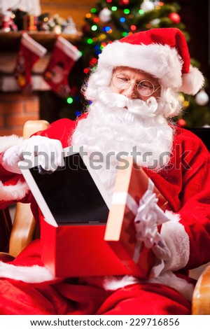 Good present! Cheerful Santa Claus putting a digital tablet into the gift box and smiling while sitting at his chair with Christmas Tree in the background