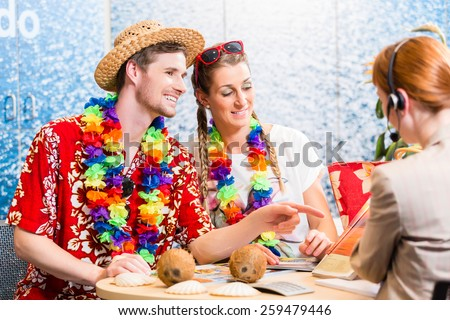 Good service in travel agency - man and woman booking a beach vacation - stock photo