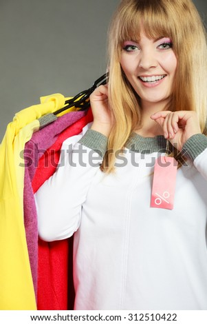 Good shopping sale concept. Blonde fashionable woman choosing clothes holding discount red label with percent sign in hand
