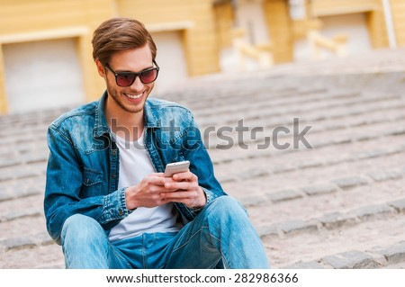 Good spending time in his city. Confident young man holding mobile phone while sitting outdoors - stock photo
