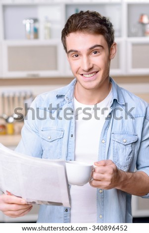 Good start of the day. Portrait of cheerful smiling young man holding newspaper and drinking coffee while feeling content